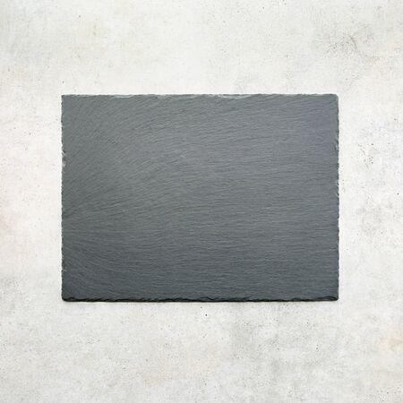 Empty slate tray on travertine stone tile background. Slate platter on light grunge stone texture, top view.