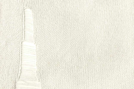 Destroy knitted fabric background. Distressed holes and rips in the white sweater knitted from cotton yarn. Banque d'images