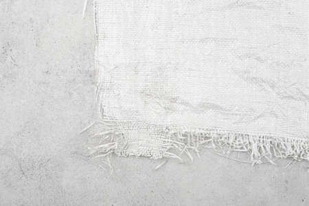 White woven plastic bag texture on stone background. Crumpled polypropylene sack cloth surface on cement.