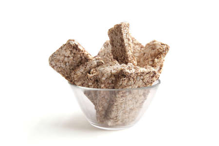 Puffed buckwheat cakes in glass bowl isolated on white background. Wholegrain crispbreads, cereal dietary crackers.