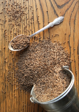 Cumin seeds on wooden background photo