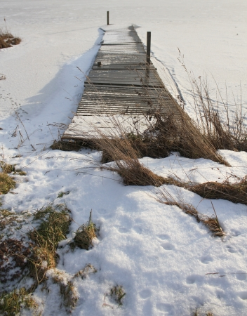 old wooden bridge on the frozen lake photo