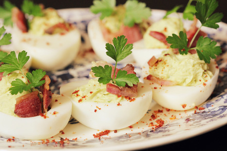 eggs and bacon: deviled eggs appetizer with avocado and bacon