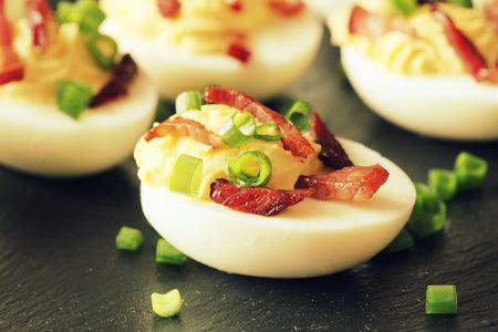 Bacon Deviled Eggs on black background Foto de archivo
