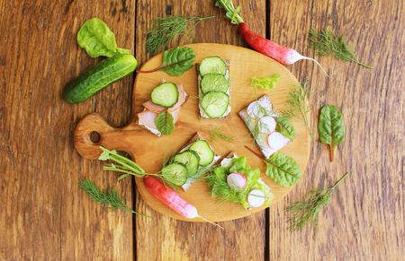 Sandwiches with various fillings. Sandwich with ham, sandwich with cucumber, cheese sandwich with radish on cutting board. Stock Photo