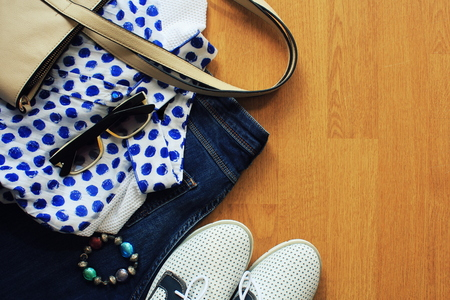 closet: Collection of womens clothes. Jeans, shoes, bluose, glass. Top view Stock Photo