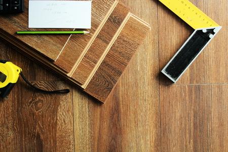 Laminaat vloerplanken en gereedschap op houten achtergrond
