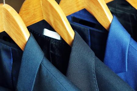 Rij van herenpakken aan het rack te koop Stockfoto