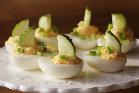 Spicy deviled eggs garnished with cucumber and leek on white plate. Wooden rustic background 스톡 콘텐츠