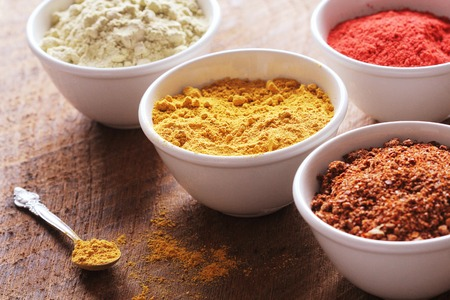Various colorful spices on wooden table in bowls . Food and cuisine ingredients.