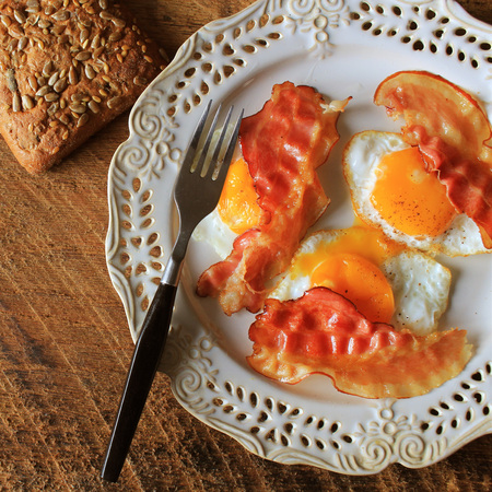 Breakfast , crispy bacon, fried eggs and bread. Sandwiches on white plate. Rustic table . Top view Stock Photo