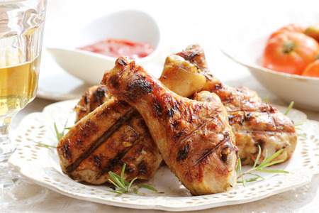 Grilled chicken legs with rosemary on table. Dinner background.