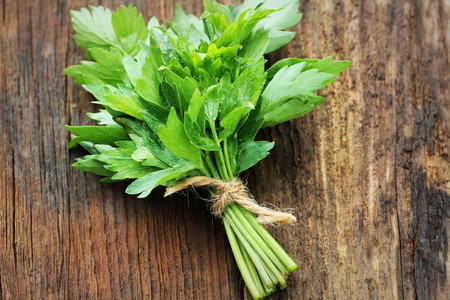 Bunch of lovage herb on wooden background .