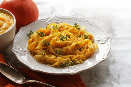 Tagliatelle pastawith pumpkin cream sauce over black background. 免版税图像