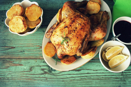 Whole roasted chicken with potatoes and lemon. Top view