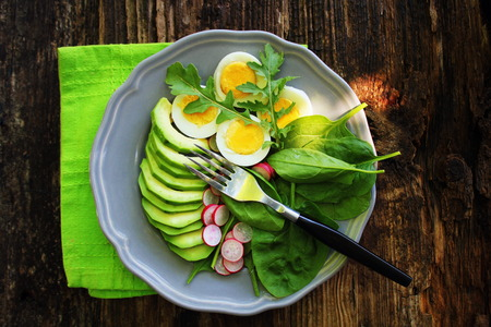 reakfast salad with radishes, boiled egg and mix lettuce leaves,spinach. Food background. Top view . Stock Photo
