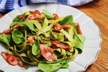 Green spinach pasta with chrispy bacon on wooden table. Gourmet italian meal . Фото со стока - 124898450
