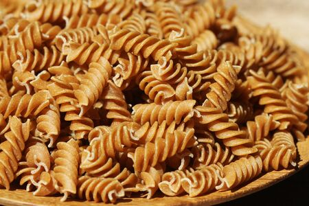 Wholemeal Fusilli in a plate. Integral Pasta over a wooden table . 免版税图像