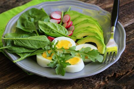 Breakfast salad with radishes, boiled egg and mix lettuce leaves,spinach. Food background. Top view