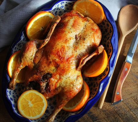 Whole crispy golden roast duck with marinated with fresh orange slices for a festive