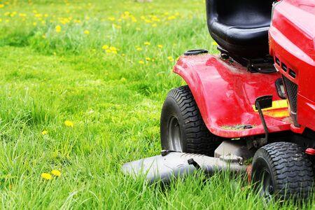 Gardener driving a riding lawn mower in a garden . Cutting grass