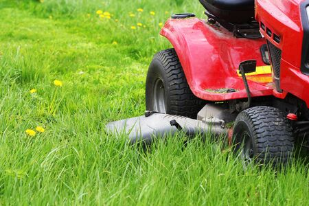 Gardening concept background. Gardener cutting the long grass on a tractor lawn mower .