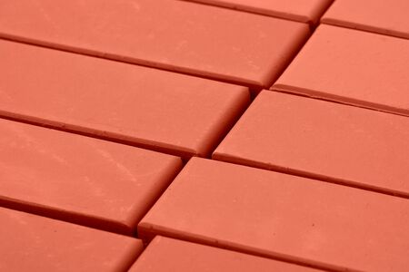 A stack of bricks for construction, hollow brick. Material for construction and repair. Clay brick, brick texture, preparation for the construction process . Фото со стока