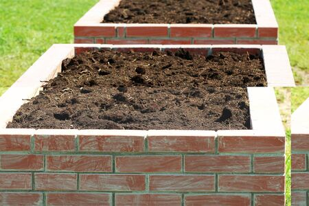 Gardening background, modern vegetable garden with raised briks beds , ready for planting .