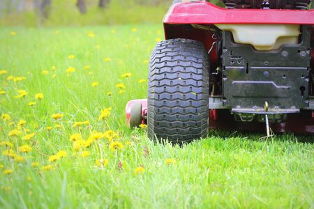 Gardening concept background. Gardener cutting the long grass on a tractor lawn mower
