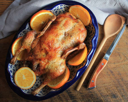 Whole crispy golden roast duck with fresh orange slices for a festive . Top view rustic wooden background