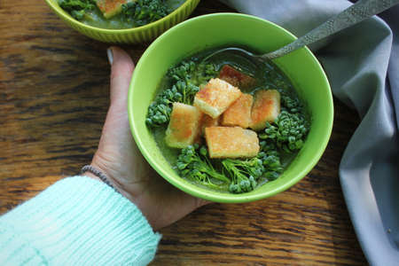 Women hand holding fresh and delicious green soup . Bowl of broccoli with croutons . Diet detox food concept. Top view, flat lay