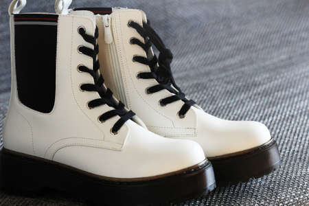 White leather winter boots on a gray background . Banco de Imagens