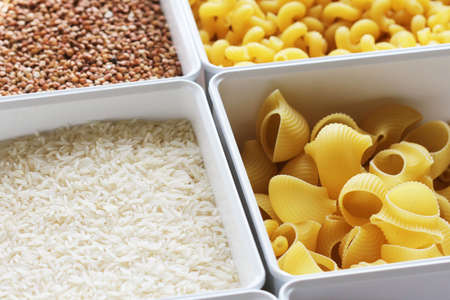 Rice, noodles, oats and buckwheat in a box. Food supplies . Banco de Imagens