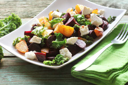 Fresh beet salad with feta cheese and fried cabbage kale .