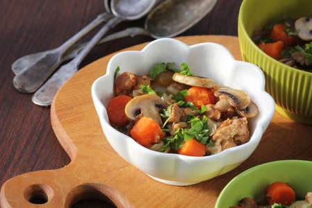 Meat stew with vegetable and mushrooms in bowl on rustic wooden background .