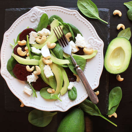 Healthy beet salad with fresh sweet baby spinach, nuts, feta cheese and avocado. Plate with salad on rustic wooden table. Top view Banco de Imagens