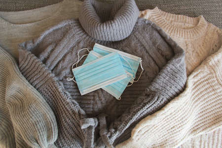 Medical face masks and three pastel warm sweaters for winter background. Women's stylish clothes. Cozy Winter look. Flat lay, top view.