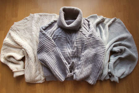 Three pastel warm sweaters for winter background. Women's stylish clothes. Cozy Winter look. Flat lay, top view.