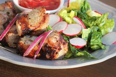 Grilled meat kebab and healthy vegetable salad of fresh radish, onion, lettuce on brown background .