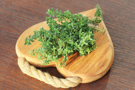 Branches of raw thyme on wooden cutting Board. Selective focus.