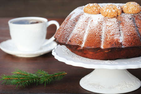 Chocolate bundt cake with icing sugar and coffee cup. Christmas background . 写真素材