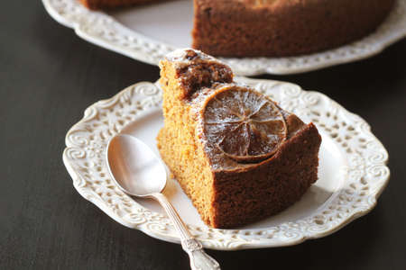 fresh baked delicious chocolate and walnuts cake with slice of orance on top