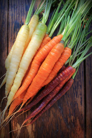 Fresh colorful carrot heap with green stems on rustic wooden background. Flat lay