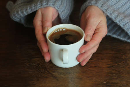 Woman's hands in sweater hold a cup of strong coffee on wooden table. Coffee fan top view background .