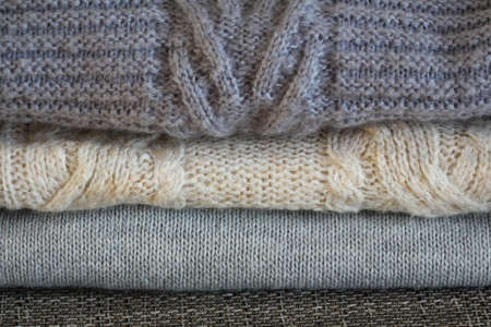 Stack of cozy knitted gray sweaters . Retro style. Warm concept . 写真素材