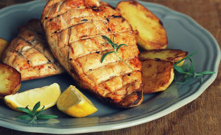 Grilled chicken breast with potatoes . Home made food. Concept for a tasty and healthy meal. Wooden background .
