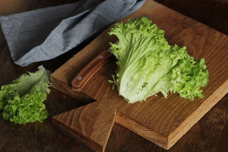Healthy eating concept. Raw green organic lettuce ready to chop on cutting board with knife.