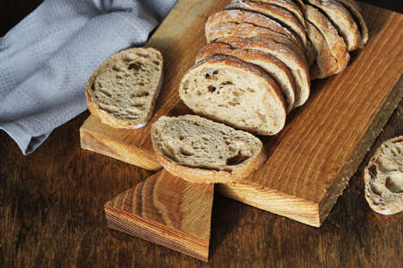 Freshly baked ciabatta bread sliced on wooden cutting board with knife .