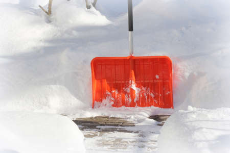 Snow cleaning concept. Red, orange shovel and snow during snowstorm. City ervice cleaning snow winter with shovel after snowstorm yard . 写真素材