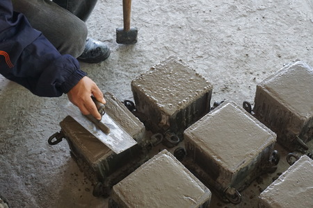 Cube Concrete Casting by steel mould and worker finishing top surface by trowel 스톡 콘텐츠